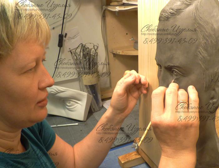Скульптор за работой над барельефом